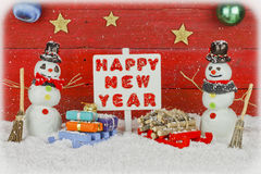 Twee sneeuwmannen die een signost met het woorden Gelukkige Nieuwjaar houden stock foto