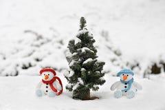 Twee sneeuwmanzitting naast een pijnboomboom Royalty-vrije Stock Foto