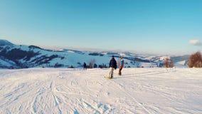 Twee snowboarders beklimt onderaan een berg stock videobeelden