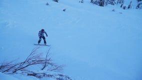 Twee snowboarders dalen onderaan de snow-covered helling in het bos stock videobeelden
