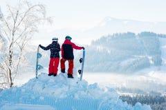 Twee snowboarders genieten van het sneeuwwitte landschap van bergen en bossen Stock Foto's