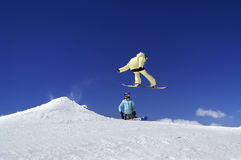 Twee snowboarders in terreinpark bij skitoevlucht op de dag van de zonwinter Royalty-vrije Stock Foto