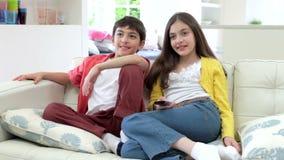 Twee Spaanse Kinderen die op Sofa Watching-TV samen zitten stock videobeelden