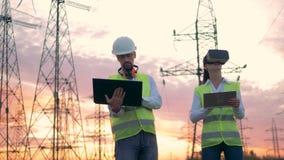 Twee specialisten stellen hun computers in werking terwijl status dichtbij machtslijnen Virtuele werkelijkheid in industrieel geb stock videobeelden