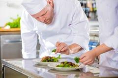 Twee specifieke chef-koks bereidt lapje vleesschotel bij gastronomisch restaurant voor stock afbeeldingen