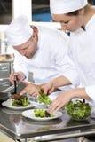Twee specifieke chef-koks bereidt lapje vleesschotel bij gastronomisch restaurant voor stock foto's