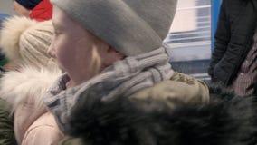 Twee speelse tienermeisjes in de winterkleren in metroauto stock videobeelden