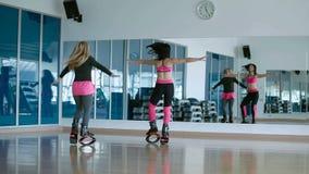 Twee sportieve meisjes die en met de kangooschoenen dansen springen stock video