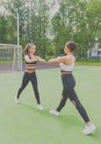 Twee sportieve meisjes die oefeningen op de Speelplaats doen Royalty-vrije Stock Fotografie