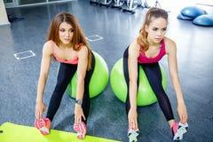 Twee sportieve meisjes die uitrekkende oefeningen doen die gymnastiekbal gebruiken royalty-vrije stock afbeelding
