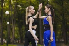 Twee sportieve meisjes verheugen zich in de overwinning terwijl het aanstoten Royalty-vrije Stock Afbeeldingen