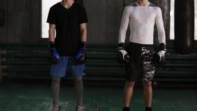 Twee sportieve, zekere jonge mannelijke boksers bevinden die in bokshandschoenen bij oude het in dozen doen gymnastiek met zandza stock footage