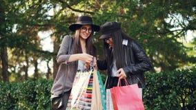 Twee spreekt jonge vrouwenshopaholics in de straat die aankopen in zakken bekijken en opwinding uitdrukken Het winkelen stock videobeelden
