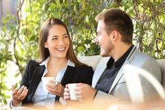 Twee stafmedewerkers die in een koffiepauze spreken stock afbeeldingen