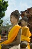 Twee standbeelden van Boedha met oranje sjaal Stock Foto's