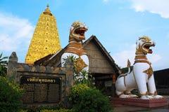 Twee standbeelden van de leeuwwacht en gouden stupa in tem Stock Fotografie