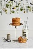 Twee stapels van koekjes, een glasfles melk, schaar en een spo stock foto's