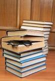 Twee stapels van oude boeken en glazen stock foto's