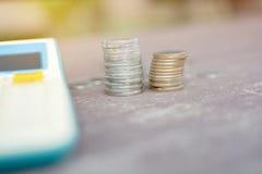 Twee stapels van zilveren muntstuk en calculator op de houten lijst Royalty-vrije Stock Afbeeldingen