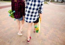 Twee stedelijke meisjes die met longboards geruite overhemden dragen die langs de straat in de stad gaan stock foto's
