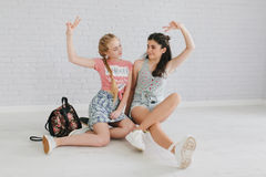 Twee stedelijke tienermeisjes die in een uitstekende ruimte stellen Royalty-vrije Stock Afbeelding