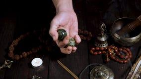 Twee steenballen in mannelijke handen en andere Tibetaanse instrumenten stock videobeelden