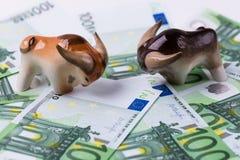 Twee stieren op EURO bankbiljetten op een witte achtergrond Concepten Financiële investering, oplopende markt stock afbeelding