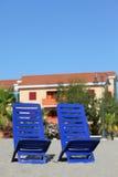 Twee stoelen bevinden zich onder zon op strand dichtbij plattelandshuisjes Royalty-vrije Stock Fotografie