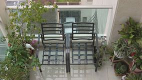 Twee stoelen en een tuin op een balkon stock videobeelden