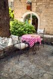 Twee stoelen en lijst aangaande de zomerterras van oud restaurant Stock Afbeeldingen