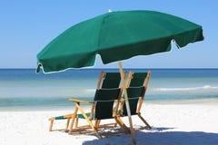 Twee stoelen en paraplu op wit zandstrand stock foto
