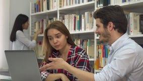 Twee studenten debatteren over iets op laptop royalty-vrije stock foto