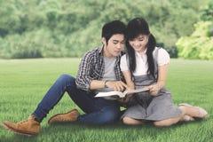 Twee studenten die een boek in het park lezen Royalty-vrije Stock Afbeeldingen