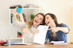 Twee studenten die examengoedkeuring vieren stock foto's