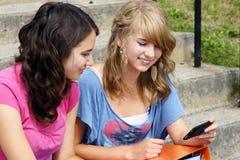 Twee studenten die op cel lezen telefoneren Stock Afbeeldingen