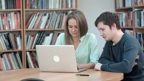 Twee studenten die samen het gebruiken van laptop bestuderen royalty-vrije stock afbeeldingen
