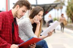 Twee studenten die wachtend vervoer in een station bestuderen Stock Foto's
