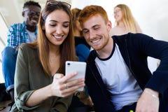 Twee studenten die zij mobiele telefoon op een universiteit gebruiken stock afbeelding