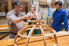 Twee studenten en een verklarende leraar in een houtbewerkingsklasse stock foto