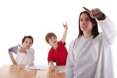 Twee studenten in het klaslokaal, om lelijke gestur te maken Stock Afbeeldingen