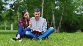 Twee studenten lezen een boek op het gazon, het flirten en het lachen stock video