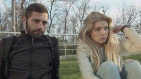 Twee studenten op de gazon jonge man en het jonge mooie meisje Het paar luistert achter de schermen aan iemand en tekens stock video