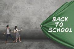 Twee studenten slepen tekst van terug naar school royalty-vrije stock afbeeldingen