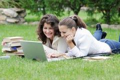 Twee studentenmeisjes met laptop Royalty-vrije Stock Afbeeldingen