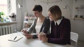 Twee studentes die tabletcomputer voor online onderwijs in huis met behulp van stock video