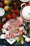 twee stukken ruw varkensvlees en verse ingrediënten Royalty-vrije Stock Afbeeldingen