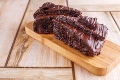 Twee stukken van chocoladecake op een houten tribune Allen op een houten achtergrond royalty-vrije stock foto's