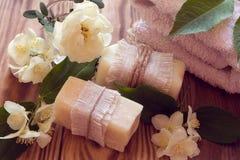 Twee stukken van droge witte zeep met handdoeken, rozen en jasmijn Stock Fotografie