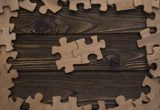 Twee stukken van het raadsel worden verbonden in het centrum op een houten textuur in een kader van stukken van een raadsel stock foto
