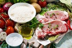 twee stukken van varkensvlees op een scherpe raad en een vers voedsel Royalty-vrije Stock Foto